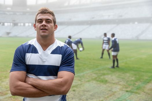 Portrait of Caucasian male rugby player standing with arms crossed in stadium. with players in the background