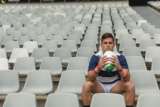 Front view of upset Caucasian male rugby player sitting with rugby ball in stadium