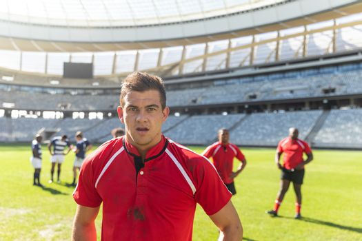 Portrait of handsome Caucasian male rugby player standing in stadium on sunny day. In the background diverse rugby players are standing.