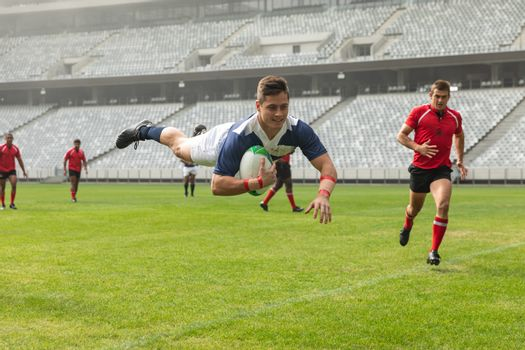 Front view of group of diverse male rugby players playing rugby in stadium