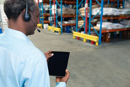 Rear view of mature African american male supervisor with headset using digital tablet in warehouse. This is a freight transportation and distribution warehouse. Industrial and industrial workers concept