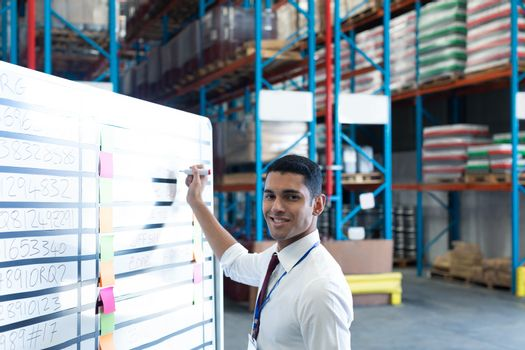Portrait of handsome young Caucasian male supervisor writing on whiteboard in warehouse. This is a freight transportation and distribution warehouse. Industrial and industrial workers concept