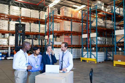 Front view of diverse staff discussing with each other in warehouse. This is a freight transportation and distribution warehouse. Industrial and industrial workers concept