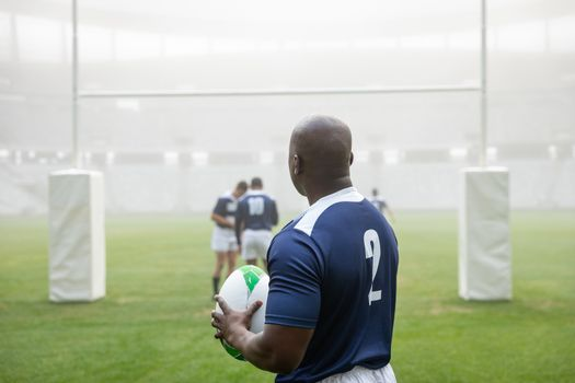 Rear view of African american male rugby player holding a rugby ball in stadium. With players in the background.