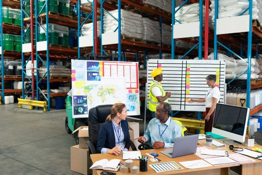 High angle view of Caucasian female manager and African-american male supervisor interacting with each other at desk in warehouse. This is a freight transportation and distribution warehouse. Industrial and industrial workers concept