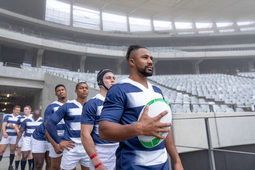 Side View of group of male rugby players entering stadium in a row for match