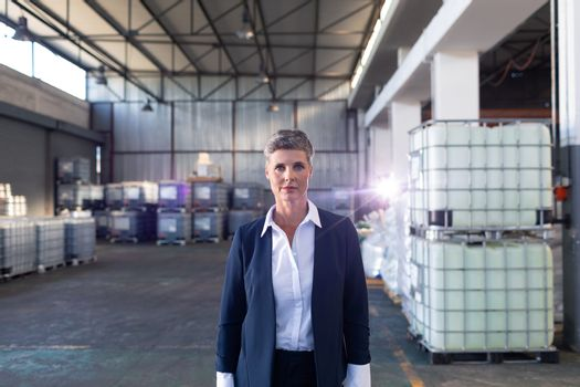 Portrait of Caucasian mature female manager standing in warehouse. This is a freight transportation and distribution warehouse. Industrial and industrial workers concept