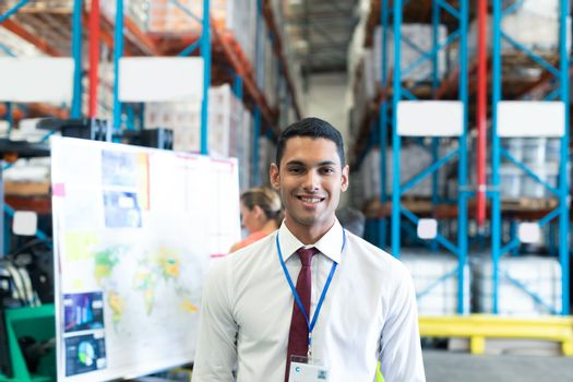 Portrait of happy Caucasian male staff looking at camera in warehouse. This is a freight transportation and distribution warehouse. Industrial and industrial workers concept