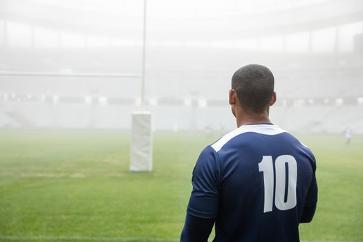Rear view of thoughtful African american male rugby player standing in stadium