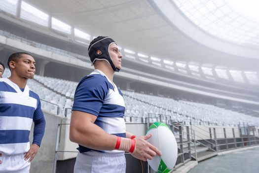 Side View of diverse male rugby player standing in a row at the entrance of stadium for match