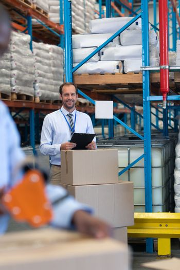 Front view of happy Caucasian male supervisor with clipboard looking at camera in warehouse. African-american staff works on the foreground. This is a freight transportation and distribution warehouse. Industrial and industrial workers concept