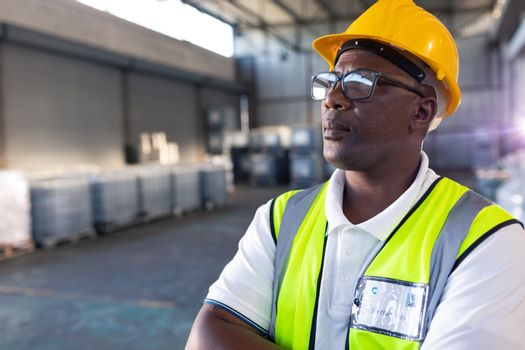 Portrait of Thoughtful African-american male staff in hardhat and reflective jacket standing with arms crossed in warehouse. This is a freight transportation and distribution warehouse. Industrial and industrial workers concept