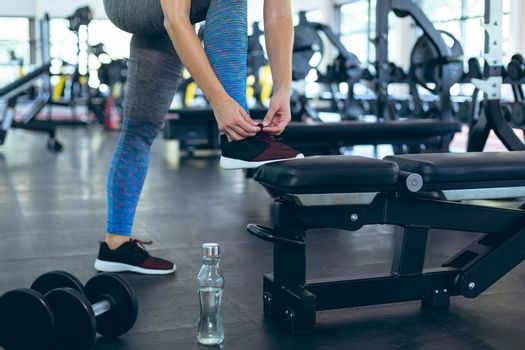 Low section of young Caucasian female athletic tying shoe laces in fitness center. Bright modern gym with fit healthy people working out and training