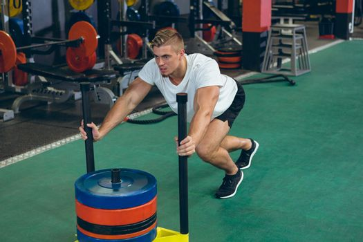 Front view of young Caucasian male athlete pushing prowler sled in fitness studio. Bright modern gym with fit healthy people working out and training