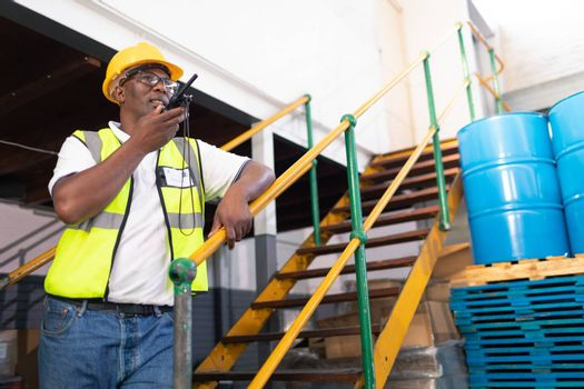 Low angle view of African-american male worker talking on talkie walkie in warehouse. This is a freight transportation and distribution warehouse. Industrial and industrial workers concept