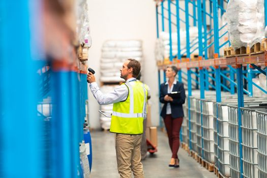 Side view of Caucasian male worker scanning package with barcode scanner in modern warehouse. Diverse staff working behind him in the aisle of the modern warehouse. This is a freight transportation and distribution warehouse. Industrial and industrial workers concept
