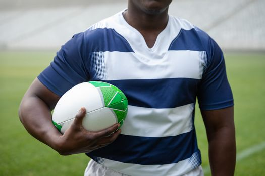 Mid section of African american male rugby player holding a rugby ball in stadium