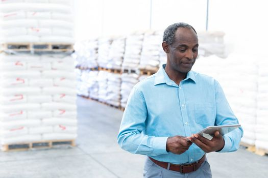 Front view of handsome mature African-american male supervisor working on digital tablet in warehouse. This is a freight transportation and distribution warehouse. Industrial and industrial workers concept
