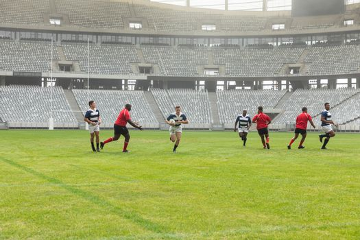 Side view of group of diverse male rugby players playing rugby in stadium