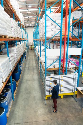 High angle view of mature Caucasian female manager working on white board in warehouse. In the end of the aisle in warehouse diverse staff are working. This is a freight transportation and distribution warehouse. Industrial and industrial workers concept