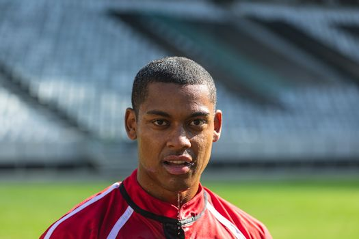 Portrait close up of tired African American male rugby player looking at camera in the stadium on a sunny day.