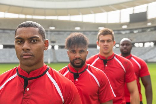 Portrait of handsome diverse male rugby players standing together while looking at the camera in stadium