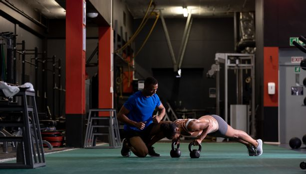 Side view of an African-American woman doing push ups with ball weights and an African-American man assisting her inside a room at a sports centre. Bright modern gym with fit healthy people working out and training. Bright modern gym with fit healthy people working out and training