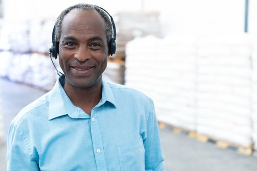 Close-up of handsome mature African-american male supervisor with headset standing in warehouse. This is a freight transportation and distribution warehouse. Industrial and industrial workers concept