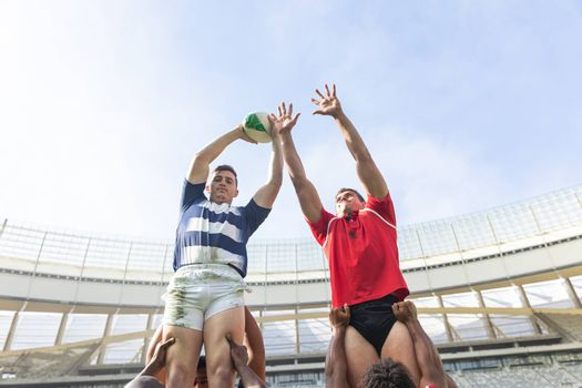 Low angle view of Caucasian male rugby players trying to catch the rugby ball in the air in stadium. Diverse rugby players helping them to catch the ball.