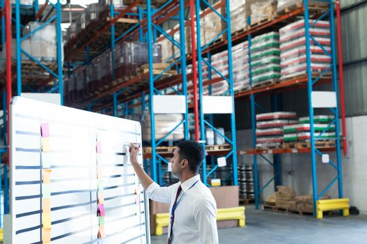 Side view of young handsome Caucasian male staff writing on whiteboard in warehouse. This is a freight transportation and distribution warehouse. Industrial and industrial workers concept