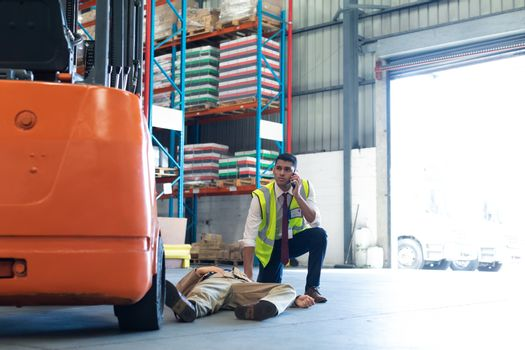 Front view of Caucasian Male supervisor talking on mobile phone while his coworker lying unconscious on the floor in warehouse. This is a freight transportation and distribution warehouse. Industrial and industrial workers concept