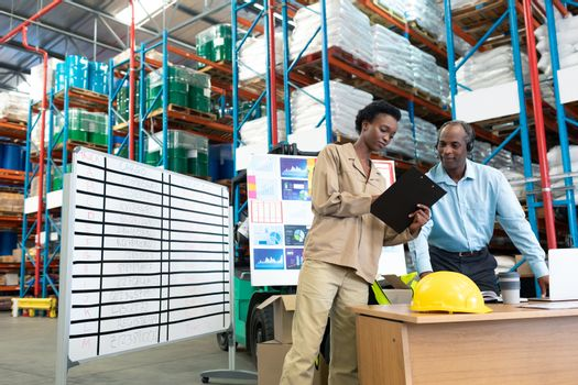 Front view of mature African-american male supervisor with beautiful young African-american female coworker discussing over clipboard at desk in warehouse. This is a freight transportation and distribution warehouse. Industrial and industrial workers concept