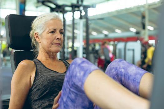 Front view of active senior Caucasian woman exercising with leg press machine in fitness studio. Bright modern gym with fit healthy people working out and training
