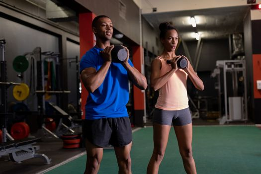 Front view of an African-American man and woman lifting ball weights with both arms inside a room at a sports centre. Bright modern gym with fit healthy people working out and training. Bright modern gym with fit healthy people working out and training