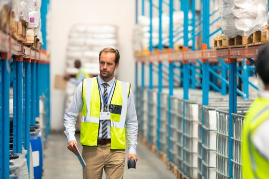 Front view of handsome mature Caucasian male supervisor walking in warehouse. This is a freight transportation and distribution warehouse. Industrial and industrial workers concept