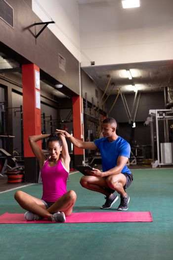 Front view of an African-American woman stretching while sitting crossed legged and an African-American man assists her inside a room at a sports center. Bright modern gym with fit healthy people working out and training. Bright modern gym with fit healthy people working out and training