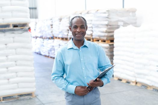 Portrait of happy mature African-american male supervisor with clipboard looking at camera in warehouse. This is a freight transportation and distribution warehouse. Industrial and industrial workers concept