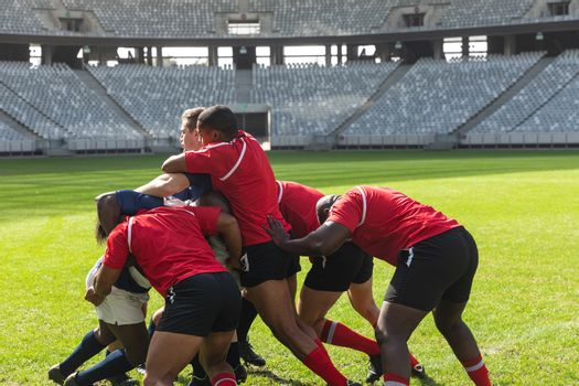 Front view of group of diverse male rugby players playing rugby match in stadium on sunny day.