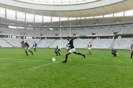 Side view of  African American male rugby player kicking rugby ball in stadium. With players in the background.