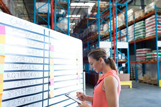 Side view of pretty young Caucasian female staff writing on clipboard near whiteboard in warehouse. This is a freight transportation and distribution warehouse. Industrial and industrial workers concept
