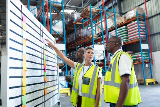 Warehouse staffs discussing over whiteboard in warehouse