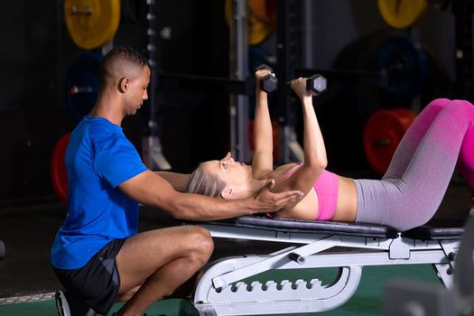 Side view of a Caucasian woman lifting dumbbells while lying on a gym bench and an African-American man assisting her inside a room at a sports centre. Bright modern gym with fit healthy people working out and training. Bright modern gym with fit healthy people working out and training