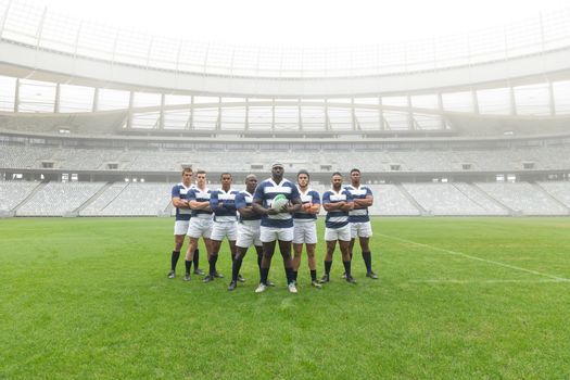 Portrait of group of diverse male rugby players standing together with rugby ball in stadium