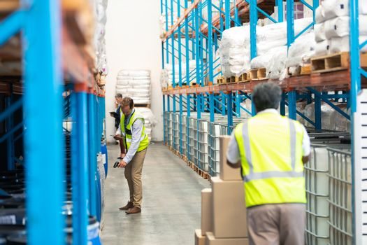 Rear view of mature Asian male worker pulling pallet jack with cardboard boxes while diverse supervisors work in the aisle in warehouse. This is a freight transportation and distribution warehouse. Industrial and industrial workers concept