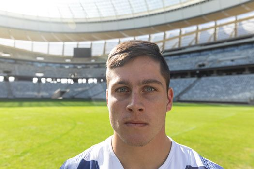 Portrait close up of handsome Caucasian male rugby player standing in stadium on sunny day.