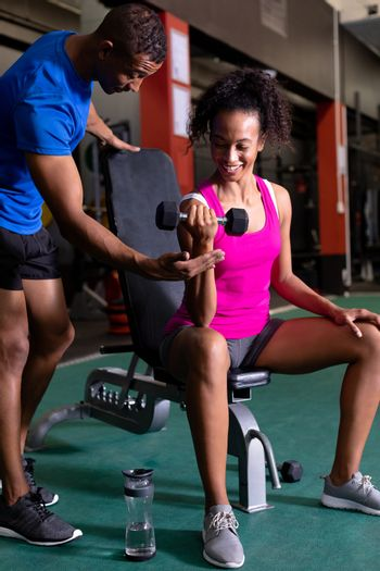 Front view of an African-American woman holding a dumbbell and an African-American man assisting her inside a room at a sports center. Bright modern gym with fit healthy people working out and training. Bright modern gym with fit healthy people working out and training