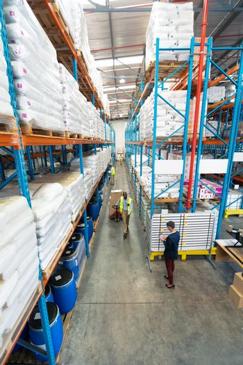 High angle view of mature diverse warehouse staff working together in warehouse. African-american man is pulling cardboard boxes. This is a freight transportation and distribution warehouse. Industrial and industrial workers concept