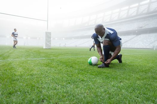 Front view of African american male rugby player tying shoelaces in the stadium. With players in the background.