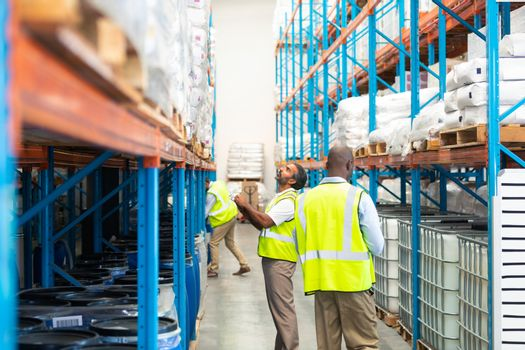 Side view of attentive mature diverse male workers in yellow vests checking stocks in warehouse. This is a freight transportation and distribution warehouse. Industrial and industrial workers concept