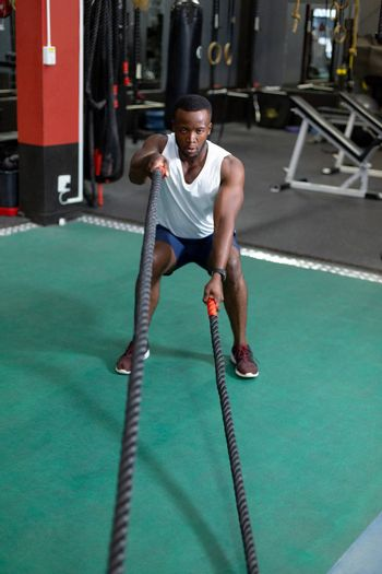 Front view of handsome concentrated fit African-american male athletic exercising with battle ropes in fitness center. Bright modern gym with fit healthy people working out and training